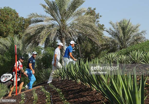 Rickie Fowler walks with Dustin Johnson both of the United States and Ryan Fox of New Zealand to the third tee during the third round of the Abu...