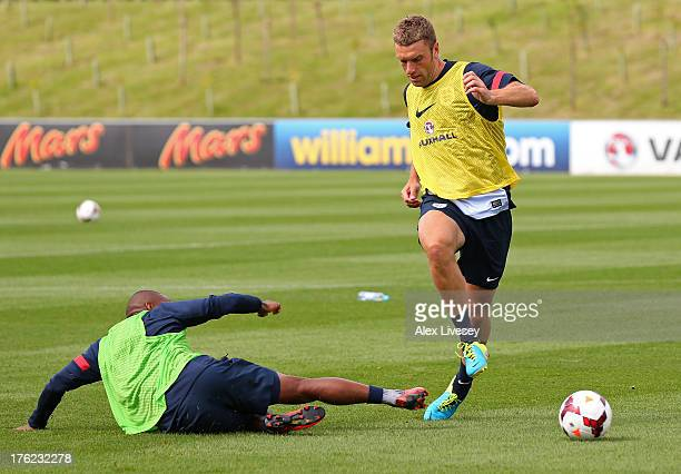 Rickie Lambert of England beats Jermain Defoe during a training session at St Georges Park on August 12 2013 in BurtonuponTrent England