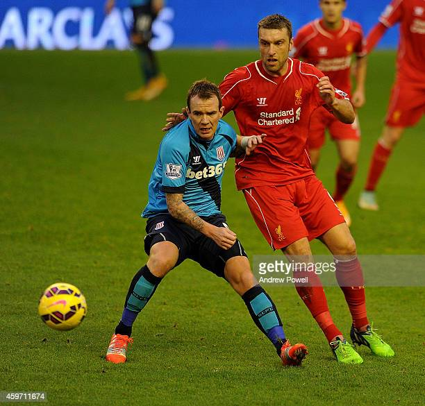 Rickie Lambert of Liverpool and Glen Whelan of Stoke City compete during the Barclays Premier Leauge match between Liverpool and Stoke City at...