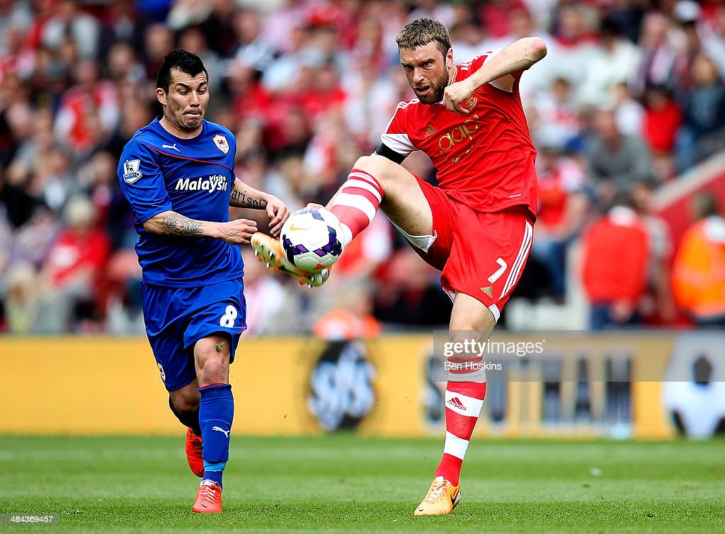 Rickie Lambert of Southampton passes under pressure from Guy Medel of Cardiff during the Barclays Premier League match between Southampton and Cardiff City at St Mary's Stadium on April 12, 2014 in Southampton, England.