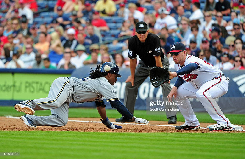 <a gi-track='captionPersonalityLinkClicked' href=/galleries/search?phrase=Rickie+Weeks&family=editorial&specificpeople=550245 ng-click='$event.stopPropagation()'>Rickie Weeks</a> of the Milwaukee Brewers dives back to first base against <a gi-track='captionPersonalityLinkClicked' href=/galleries/search?phrase=Freddie+Freeman&family=editorial&specificpeople=5743987 ng-click='$event.stopPropagation()'>Freddie Freeman</a> of the Atlanta Braves at Turner Field on April 15, 2012 in Atlanta, Georgia. All uniformed team members are wearing jersey number 42 in honor of Jackie Robinson Day.