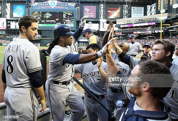 Rickie Weeks of the Milwaukee Brewers highfives Jonathan Lucroy and Corey Hart in the dugout after Weeks hit a solo home run against the Arizona...