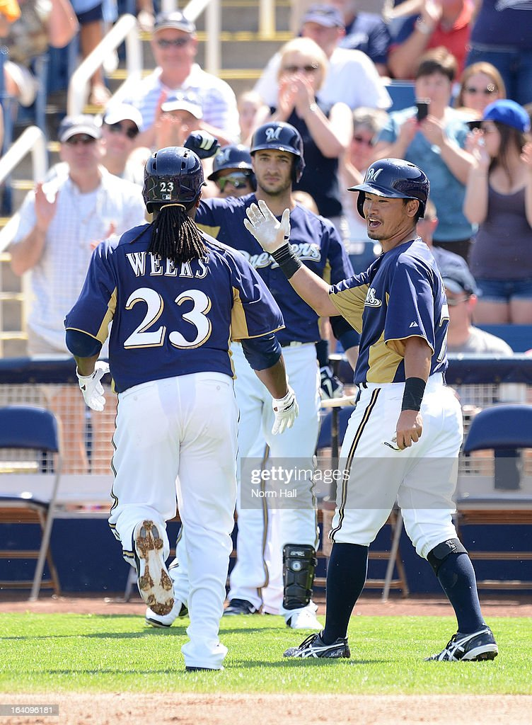 <a gi-track='captionPersonalityLinkClicked' href=/galleries/search?phrase=Rickie+Weeks&family=editorial&specificpeople=550245 ng-click='$event.stopPropagation()'>Rickie Weeks</a> #23 of the Milwaukee Brewers is congratulated by teammates <a gi-track='captionPersonalityLinkClicked' href=/galleries/search?phrase=Norichika+Aoki&family=editorial&specificpeople=850957 ng-click='$event.stopPropagation()'>Norichika Aoki</a> #7 and Ryan Braun #8 after hitting a home run against the Los Angeles Angels of Anaheim at Maryvale Baseball Park on March 19, 2013 in Maryvale, Arizona.
