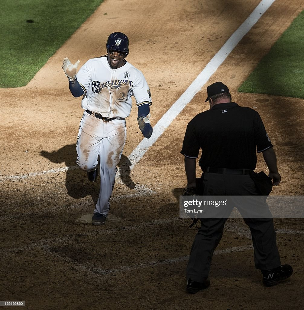 Rickie Weeks #23 of the Milwaukee Brewers scores the winning run on a sacrifice fly by Jonathan Lucroy #20 of the Brewers in the tenth inning on opening day at Miller Park on April 1, 2013 in Milwaukee, Wisconsin. Lucroy's sacrifice fly came off of Adam Ottavino #0 of the Colorado Rockies as the Milwaukee Brewers went on to defeat the Colorado Rockies 5-4.
