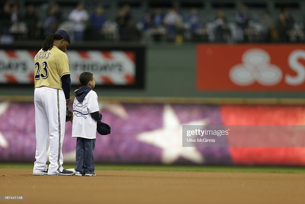 Rickie Weeks #23 of the Milwaukee Brewers stands next to a fan during the playing of out National Anthem before the game against the Chicago Cubs at Miller Park on April 21, 2013 in Milwaukee, Wisconsin.