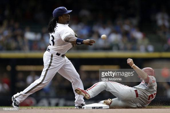 Rickie Weeks of the Milwaukee Brewers try to turn the double play as Kevin Frandsen of the Philadelphia Phillies slides into second base during the...