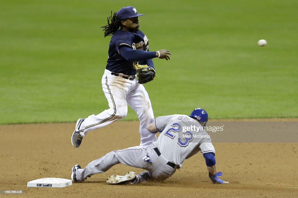 <a gi-track='captionPersonalityLinkClicked' href=/galleries/search?phrase=Rickie+Weeks&family=editorial&specificpeople=550245 ng-click='$event.stopPropagation()'>Rickie Weeks</a> #23 of the Milwaukee Brewers turns the double play as <a gi-track='captionPersonalityLinkClicked' href=/galleries/search?phrase=Craig+Gentry&family=editorial&specificpeople=6352553 ng-click='$event.stopPropagation()'>Craig Gentry</a> #23 of the Texas Ranger slides into second base in the top of the seventh inning at Miller Park on May 07, 2013 in Milwaukee, Wisconsin.