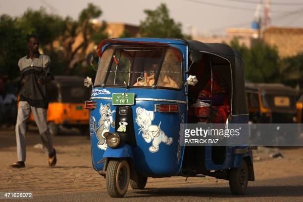 A rickshaw also known as 'Tuktuk' is decorated with toys and different Disney characters in Khartoum on April 16 2015 AFP PHOTO / PATRICK BAZ