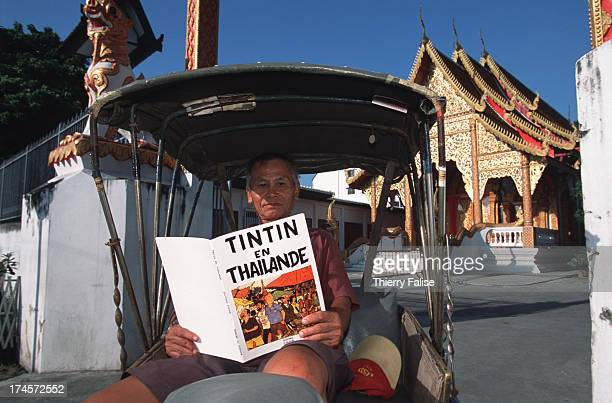 A rickshaw driver is reading 'Tintin in Thailand' a parody of the adventures of the famous Belgian cartoon reporter