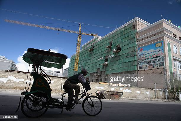 A rickshaw driver passes by a construction site for a new hotel in the new part of Lhasa city on August 6 2006 in Lhasa of Tibet Autonomous Region...