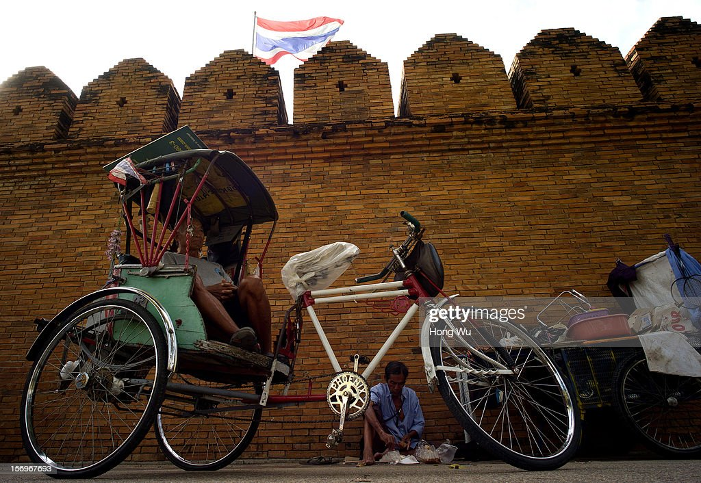 A rickshaw driver rests beside original city wall at Tha Phae Gate on November 25, 2012 in Chiang Mai, Thailand. Chiang Mai is the largest and most culturally significant city in northern Thailand. It's a former capital of the Kingdom of Lanna (1296 - 1768) and was the tributary Kingdom of Chiang Mai from 1774 until 1939. In recent years, it has become an increasingly modern city and has been attracting over 5 million visitors each year, of which between 1.4 million and 2 million are foreign tourists.