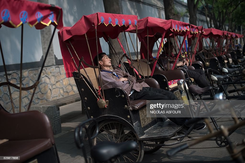 A rickshaw driver takes a nap as he waits for customers on a street in Beijing on April 29, 2016. / AFP / NICOLAS