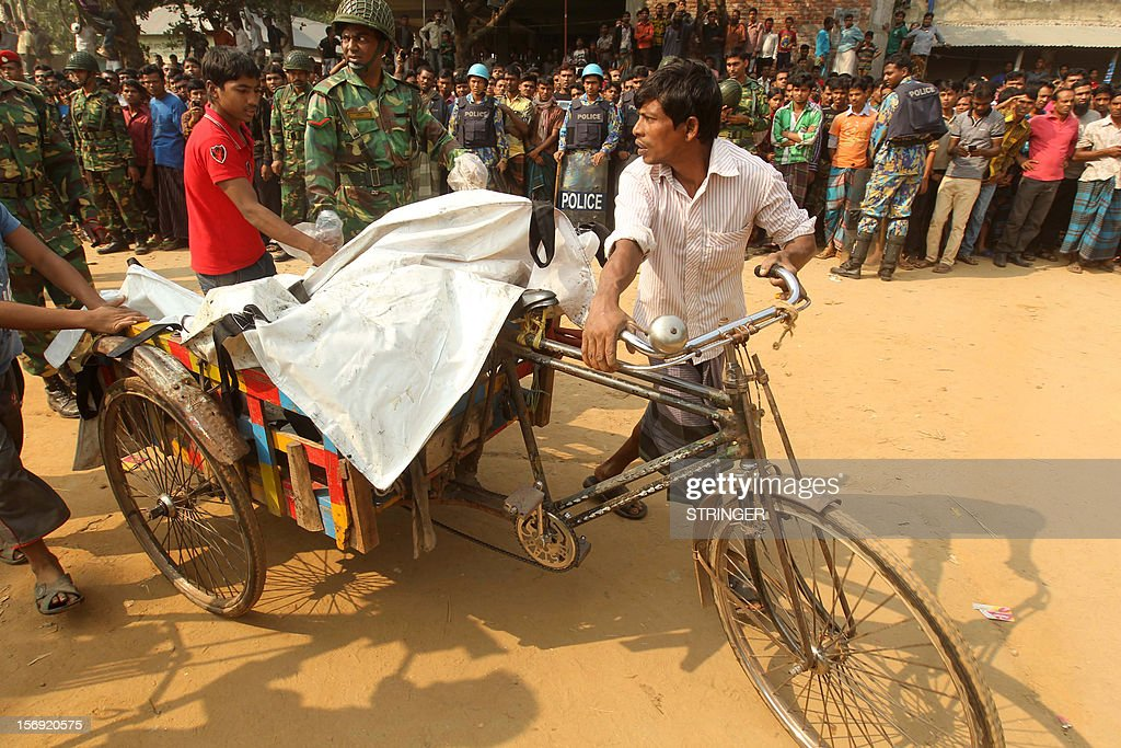 A rickshaw driver transports bodies of victims who died in a fire in the nine-storey Tazreen Fashion plant in Savar, about 30 kilometres north of Dhaka on November 25, 2012. Rescue workers in Bangladesh recovered 109 bodies on Sunday after a fire tore through a garment factory, forcing many workers to jump from high windows to escape the smoke and flames. AFP PHOTO