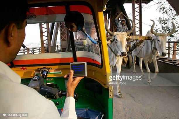 Rickshaw driver using satellite navigation device on bridge