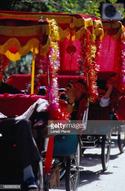 Rickshaw drivers rest on the banks of Qianhai Lake in Doncgcheng, Beijing.