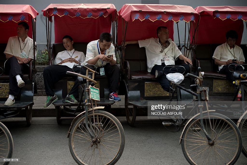Rickshaw drivers wait for customers on a street in Beijing on April 29, 2016. / AFP / NICOLAS
