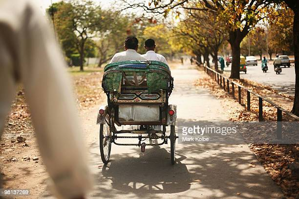 A rickshaw is riden down a pathway beside a busy road on March 25 2010 in Chandigarh India
