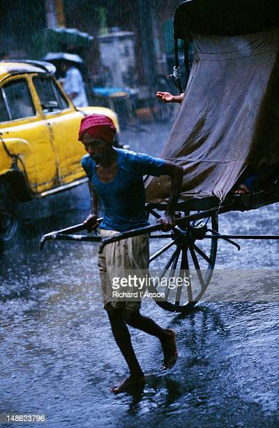 Rickshaw on street during monsoon with hand of passenger checking for rain.