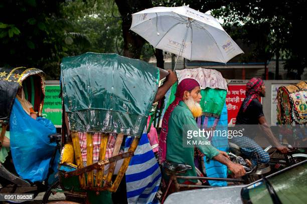 Rickshaw passenger hold umbrella for protect rickshaw puller heavy rainfall made in Dhaka city The death toll rises to 156 in several hill districts...