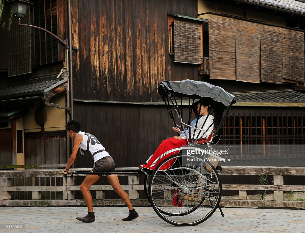 A rickshaw puller carries tourists at Gion street on July 5, 2014 in Kyoto, Japan. Kyoto has been named the world's best city in the U.S. magazine Travel + Leisure for 2014, according to its website. The former capital of Japan is known for old temples and shrines.
