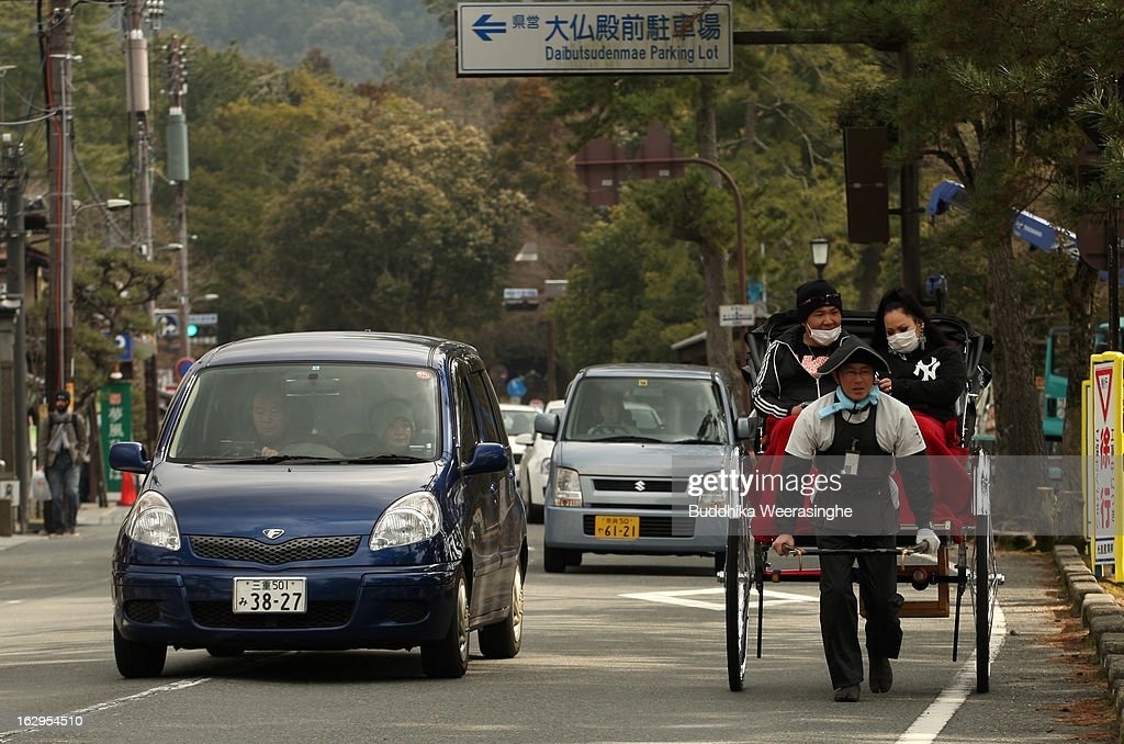 A rickshaw puller carries tourists on March 2,2013 in Nara, Japan. The city of Nara is ancient capital of Japan and is the location of seven sites to be listed as UNESCO World Heritage Sites.