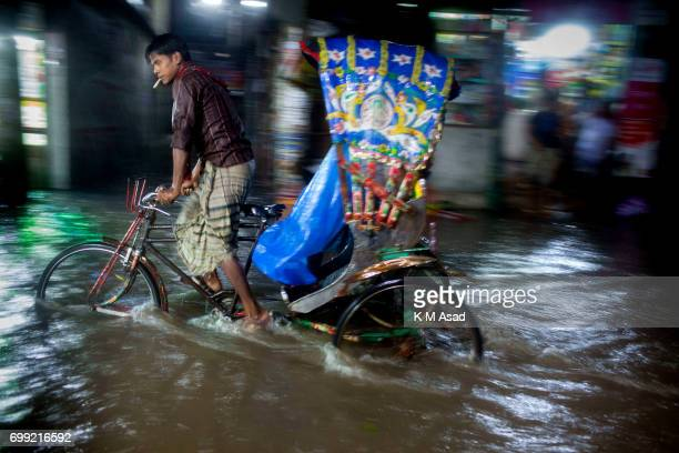 Rickshaw puller carry passenger when heavy rainfall made waterlogging in Dhaka city The death toll rises to 150 in several hill districts including...