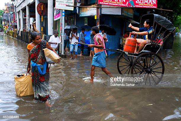 A rickshaw puller carrying passenger in a waterlogged street in Kolkata Heavy rains resulted in water logging in many parts of Kolkata India with...