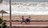 A rickshaw puller goes about his business with tourists on a ride at the Durban beach in Durban on March 5 2012 as huge waves caused by tropical...