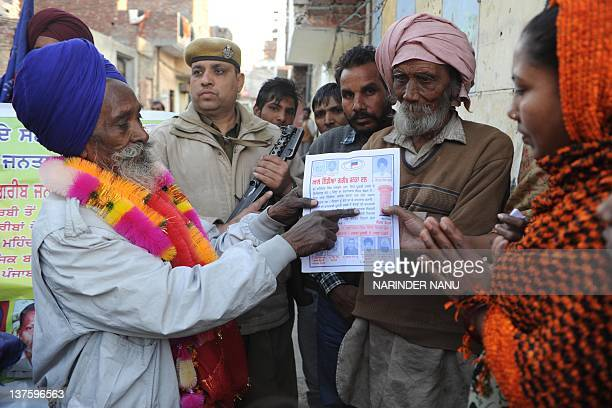 Rickshaw puller Mahinder Singh from the All India Garib Janta Dal party and candidate for the Member of Legislative Assembly shows his pamphlet to...