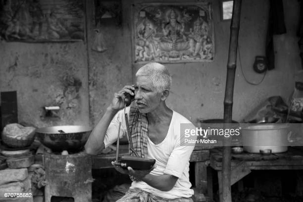 A rickshaw puller making a phone call to his family who are back in the village September 22 2010 in Kolkata India Kolkata has approximately 18000...