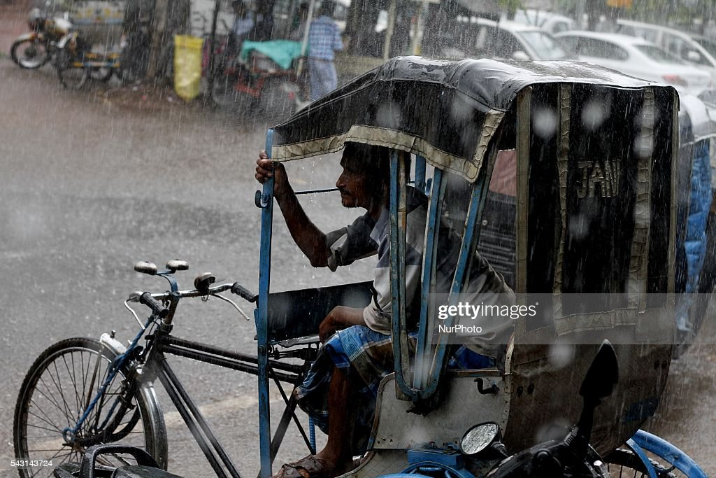 A rickshaw puller sits at his parked cycle rickshaw and waits for customers as it rains in the eastern Indian city Bhubaneswar, India, Sunday, 26 June 2016.