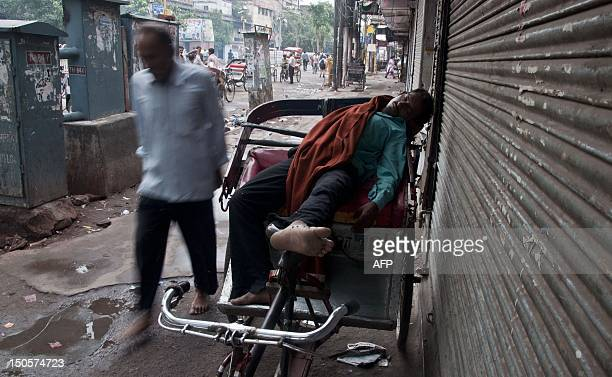 A rickshaw puller sleeps on his vehicle at the old quarters of New Delhi on August 22 2012 The last census in 2001 estimated that there were 778599...