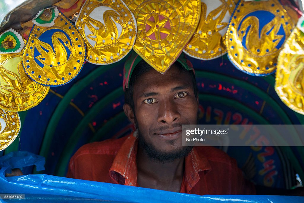 A rickshaw puller take shelter inside his rickshaw during rain in Dhaka, Bangladesh on May 28, 2016.