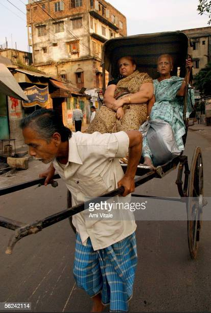 A rickshaw puller takes two Indian women shopping November 19 2005 in Calcutta in the state of West Bengal in India One of the oldest vehicles in the...