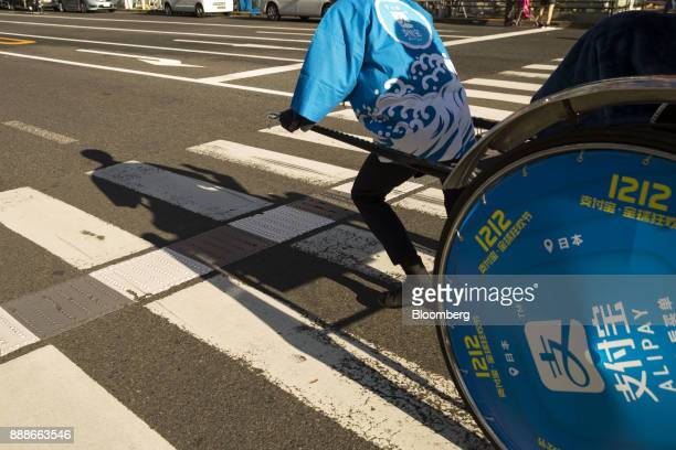 A rickshaw puller transports a customer during a campaign event for Ant Financial Services Group's Alipay an affiliate of Alibaba Group Holding Ltd...