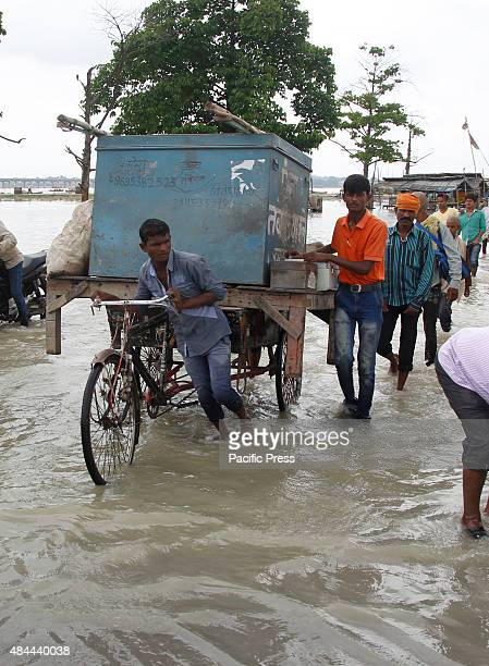 A rickshaw puller transports priests' belongings from the flooded banks of river Ganga after heavy monsoon rains that caused the rise in water levels...