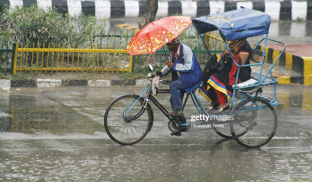 A rickshaw puller trying to protect himself from showers with umbrella on February 5, 2013 in Noida, India. The persistent rains since late last night break the seven decade old record for the highest rainfall in a single day in February in Delhi-NCR.