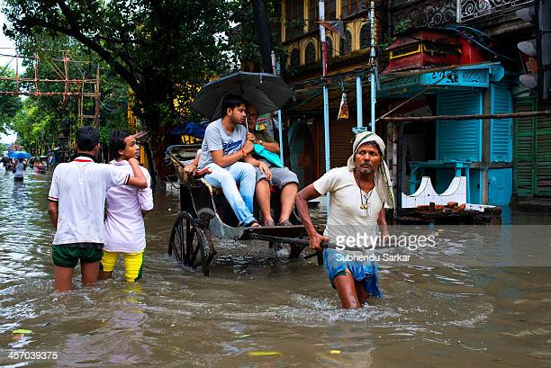 CONTENT] A rickshaw puller wades through a flooded street in Kolkata as he carries two passengers