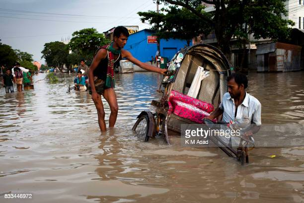 AGRABAD DHAKA CHITTAGONG BANGLADESH A rickshaw struggles through a flooded area of Chittagong People traveling in flooded areas in Chittagong...