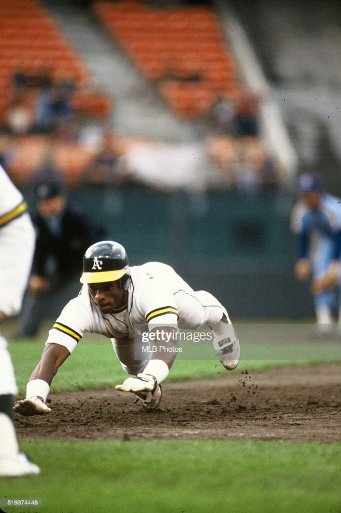 Ricky Henderson #24 of the Oakland Athletics dives back into first base during an American League game on an unknown date at Oakland-Alameda County Coliseum, in Oakland, California.