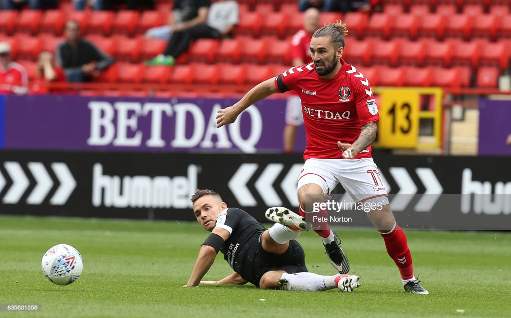 Ricky Holmes of Charlton Athletic moves past the challenge of Billy Waters of Northampton Town during the Sky Bet League One match between Charlton Athletic and Northampton Town at The Valley on August 19, 2017 in London, England.