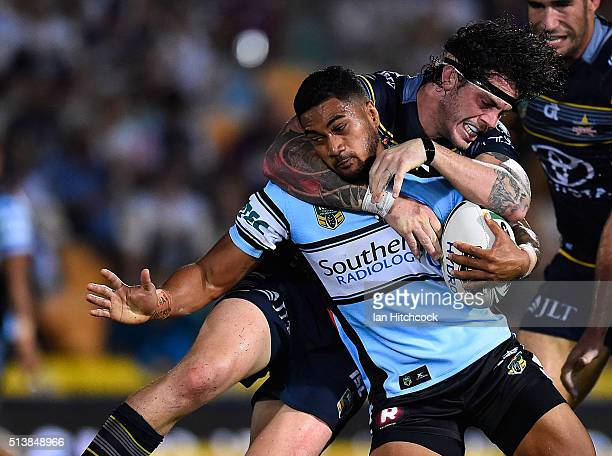 Ricky Leutele of the Sharks is tackled by Ethan Lowe of the Cowboys during the round one NRL match between the North Queensland Cowboys and the...