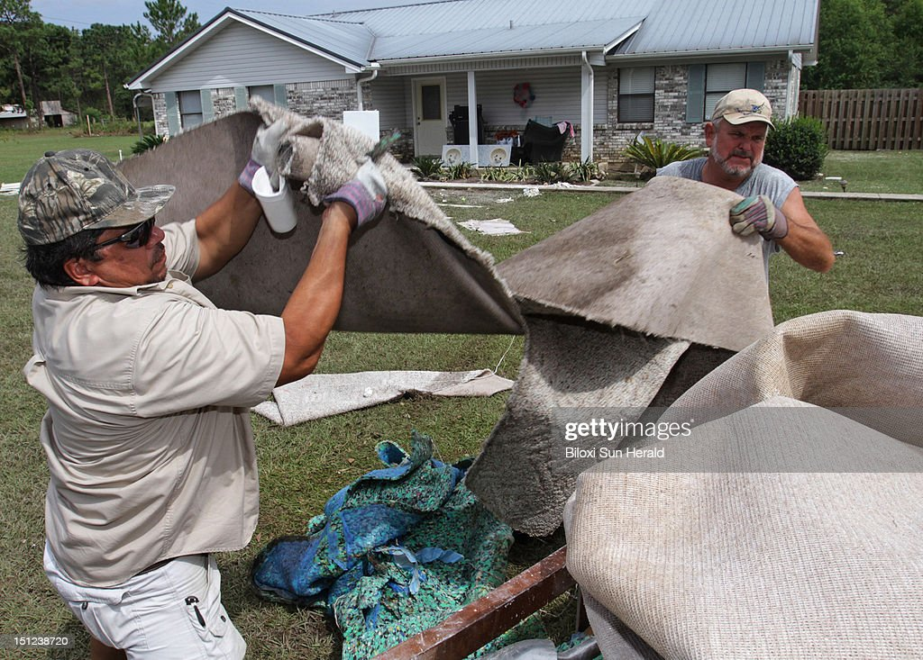 Ricky Nix of Vancleave, Miss., right, helps Bob Poppenhouse throw out wet carpeting at his house in the Helena, Mississippi, community in Jackson County on Tuesday September 4, 2012 after Hurricane Isaac caused flooding in the area.