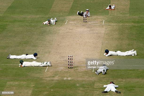 Ricky Ponting and Matthew Hayden of Australia lie on the ground along with the Indian players and umpire Billy Bowden as a swarm of bees pass over...