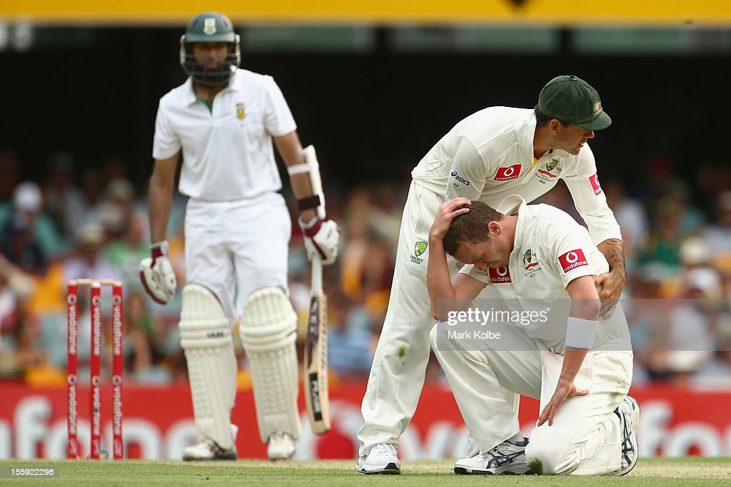 Ricky Ponting of Australia helps his team mate Peter Siddle of Australia to his feet after he dropped a caught and bowled chance from Hashim Amla of South Africa only to have it over rules due to a no-ball during day one of the First Test match between Australia and South Africa at The Gabba on November 9, 2012 in Brisbane, Australia.