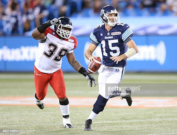 Ricky Ray of the Toronto Argonauts is about to have the ball knocked away by Charleston Hughes of the Calgary Stampeders during a CFL game at the...
