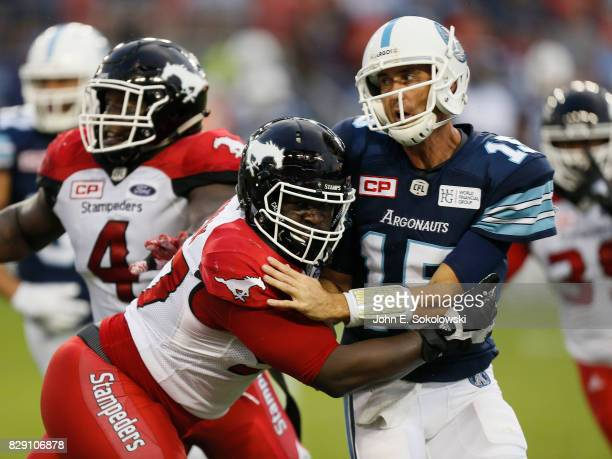 Ricky Ray of the Toronto Argonauts is hit by Derek Wiggan of the Calgary Stampeders after throwing a pass during a CFL game at BMO Field on August 3...