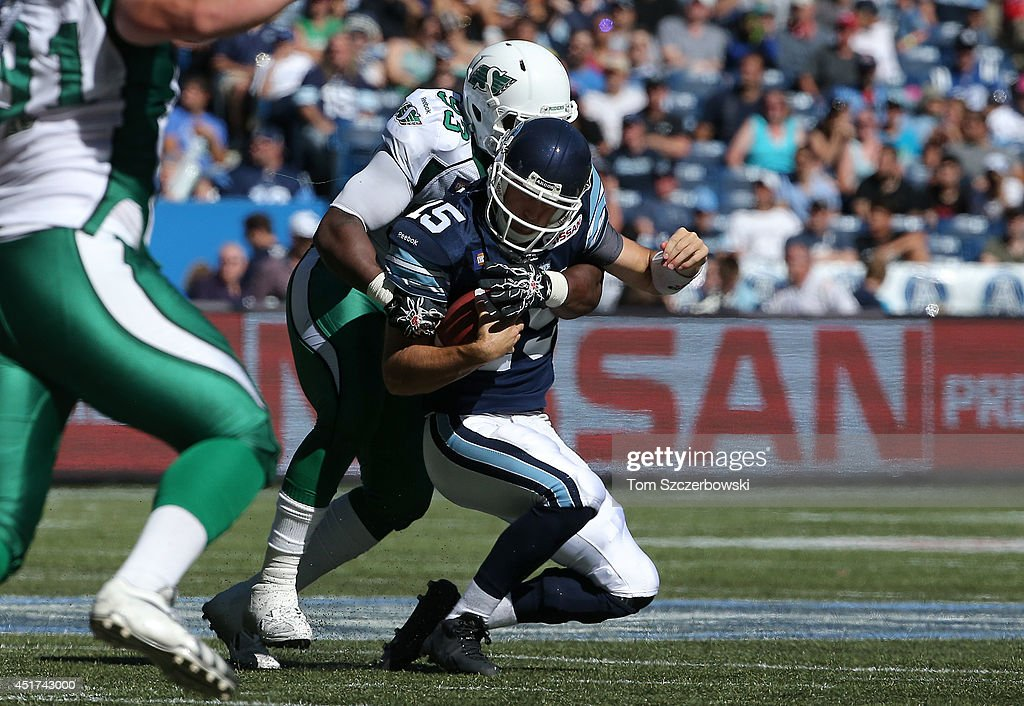<a gi-track='captionPersonalityLinkClicked' href=/galleries/search?phrase=Ricky+Ray&family=editorial&specificpeople=4171123 ng-click='$event.stopPropagation()'>Ricky Ray</a> #15 of the Toronto Argonauts is sacked by Tearrius George #93 of the Saskatchewan Roughriders during a CFL game on July 5, 2014 at Rogers Centre in Toronto, Ontario, Canada.