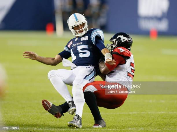Ricky Ray of the Toronto Argonauts is tackled by Charleston Hughes of the Calgary Stampeders during a CFL game at BMO Field on August 3 2017 in...