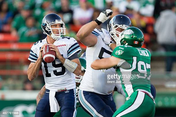 Ricky Ray of the Toronto Argonauts looks to throw under pressure from John Chick of the Saskatchewan Roughriders in a game between the Toronto...